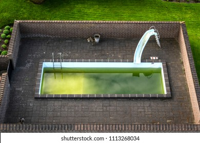 Swimming pool in a public park with green water and a slide surrounded by a brick wall