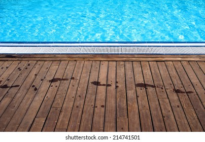 Swimming pool showing the wooden poolside with wet footprints