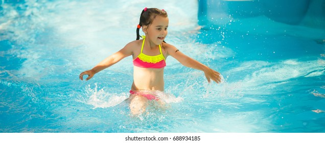 Swimming pool slides for children on water slide at aquapark . Summer kid holiday outdoor. Little girl in aqua park.