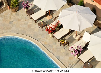 Swimming pool in small hotel yard with parasols and chaise-longues