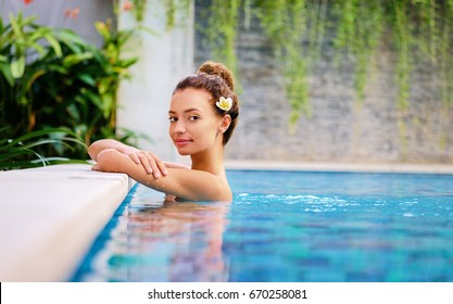 Swimming pool spa retreat relaxation. Relaxing woman enjoying serenity in summer holiday travel vacation at resort hotel.