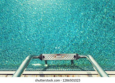 Swimming pool stair grab bars ladder at hotel deck floor., Summer holidays relaxation activity on the beach., Outdoor stainless steel handrail ladder.,Vacation leisure concept