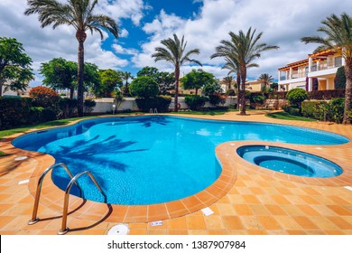 Swimming pool with stair. Grab bars ladder in the blue swimming pool. Poolside with blue clear water and ladder. Stair at the side of swimming pool, summer concept.
