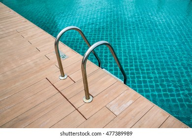Swimming pool with stair and wooden deck .