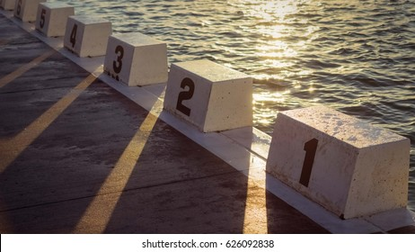 Swimming Pool - Starter blocks of ocean pool with sun rays.
