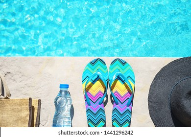 Swimming pool and straw hat, colorful flip flops, wicker bag, straw hat, bottle with still water as sunny summer background. Travel holiday suntan vacation concept. Flat lay, top view, close up.