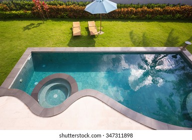 Swimming pool with sun chairs in luxury hotel villa in tropics. Sunny day, vacation and travel