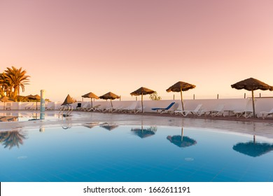 Swimming pool with sunbeds and umbrellas reflected in the water at sunset, Tunisia