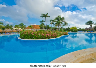 Swimming pool with the tropical style island and dark blue sky and water at the luxury caribbean, mexican resort.