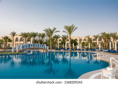 Swimming pool with turquoise water and sun loungers at the resort in Egypt. Bridge over the pool
