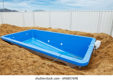 Swimming pool under construction.Installation plastic fiberglass pool in the ground at house backyard. Construction site