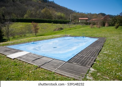 swimming pool with wooden curb closed and covered with blue tarp in Spring green meadow rounded by mountains in Nature in Asturias Spain Europe