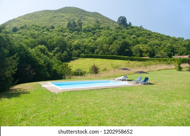 swimming pool with wooden curb, umbrellas and hammocks, in green meadow garden rounded by mountains in Nature of Asturias Spain Europe