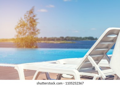 Swimming pool with wooden deck at hotel.Summer sunny day. Lounge chairs, beach sunbeds in a swimming pool invite you to relax