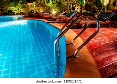 Swimming pool with wooden deck and stair. Romantic evening lighting setting near the pool, has landscaped gardens with tropical flora and plenty of comfortable sunbeds