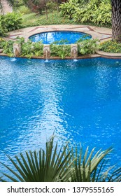 Swimming pools surrounded by palm trees and lush evergreen in a tropical plants garden