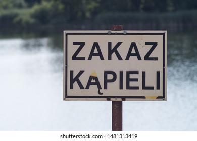 """""""Swimming prohibited"""". Sign near the lake. Polish language."""