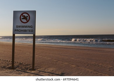 Swimming prohibited sign on empty sandy beach at sunrise