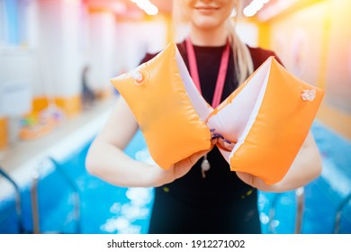 Swimming school for children, woman trainer holds inflatable armbands for kids accessories.