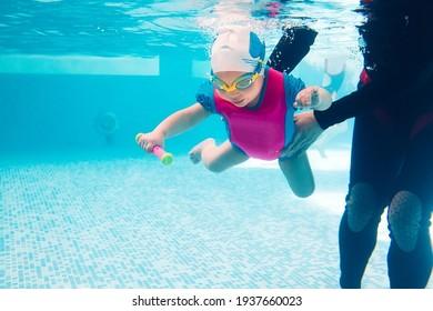 A swimming teacher teaches a kid to swim in the pool