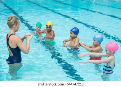 Swimming trainer instructing students in pool
