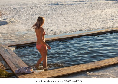 Swimming in the winter. Woman enters ice bathing water