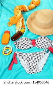 Swimsuit and beach items on bright blue background