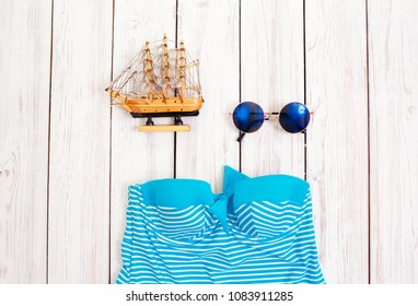 swimsuit, glasses on a light wooden background. Everything for rest