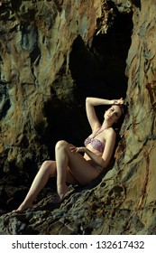 Swimsuit model posing sexy in front of black lava field on at Palos Verdes, CA