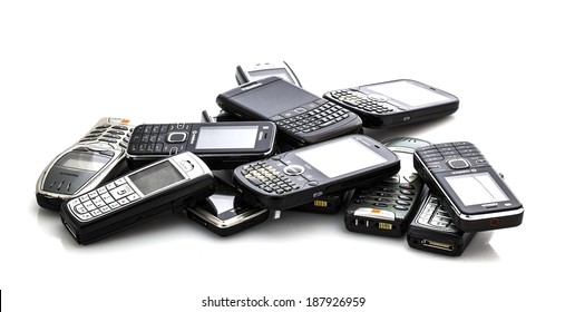 SWINDON, UK - APRIL 18, 2014: Pile of Old Moblie Phones ready for recycling on a white background