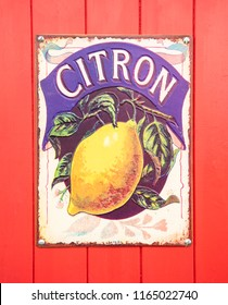 SWINDON, UK - AUGUST 18, 2018: Old Citron Enamel sign on a red wooden background