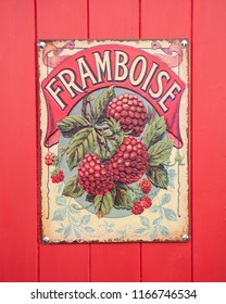 SWINDON, UK - AUGUST 18, 2018: Old Retro Enamel Framboise sign on a red wooden Background