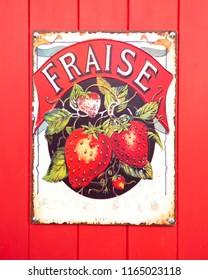 SWINDON, UK - AUGUST 26, 2018: Old Fraise, Enamel sign on a red wooden background