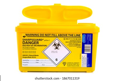 SWINDON, UK - DECEMBER 4, 2020: Yellow Sharpsguard biohazard medical contaminated sharps clinical waste container isolated on white background