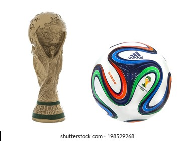 """SWINDON, UK - JUNE 11, 2014: FIFA World Cup Trophy and Adidas Brazuca Football on a white Background,  """"FIFA World Cup Trophy"""", was introduced in 1974. Made of 18 carat gold with a malachite base"""