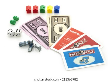 SWINDON, UK - JUNE 11, 2014: English Edition of Monopoly showing Money, Cards, Houses, Dice and Markers,  The classic trading game from Parker Brothers was first introduced to America in 1935.