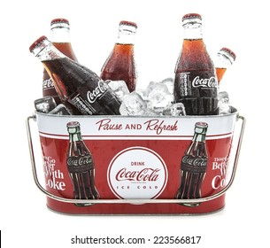 SWINDON, UK - MARCH 29, 2014: Cold Classic Coke Bottes in a Coca-Cola Ice bucket on a white background