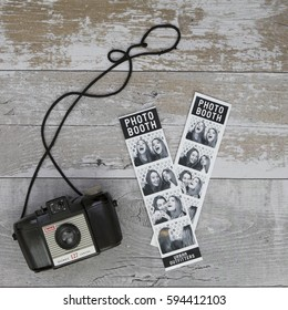 SWINDON, UK - MARCH 6, 2017: Photo Booth Film Strips on a wooden background with an old Kodak 127 camara