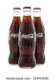 SWINDON, UK - MAY 21, 2014: Three Classic Coke Bottes on a white background