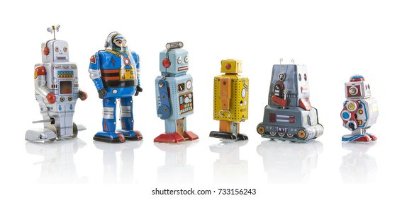SWINDON, UK - OCTOBER 12, 2017: Row of old clockwork tin robots in a line on a white background