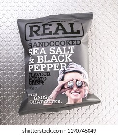 SWINDON, UK - SEPTEMBER 28, 2018: A Packet of REAL Handcooked Sea Salt and Pepper Flavour Potato Crisps on a silver backgound.