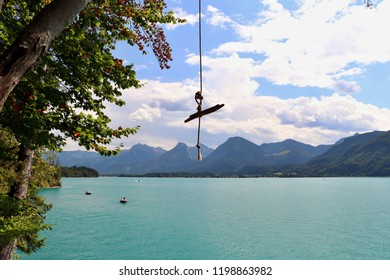 A swing above a lake with Alps mountains in the background. Location: Europe, Austria, Wolfgangsee lake
