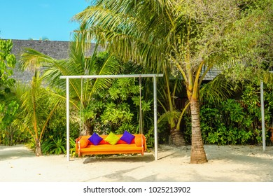 A swing against the backdrop of an exotic palm scenery on one of the Maldivian islands