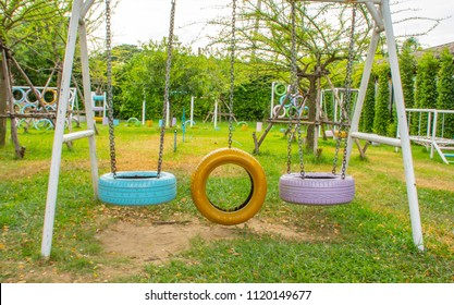 Swing chairs made from old tires  for children in park.