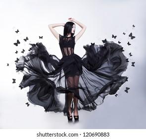 Swing. Flutter. Sensual Woman in Black Evening Fluttering Dress with Butterflies