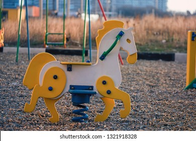 Swing horse toy for kids on a children's playground. Swing for children on a kids playground. Yellow horse swing for kids. Children playground with a wooden horse swing.