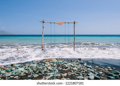 A swing in the middle of the ocean at a blue stone beach