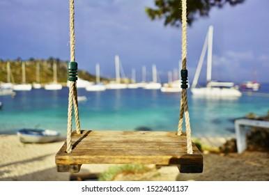 Swing on the beach in Agios Nikolaos Harbour, Zakynthos Island. Europe, Greece.
