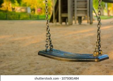 Swing on children's playground, blurry playground in background