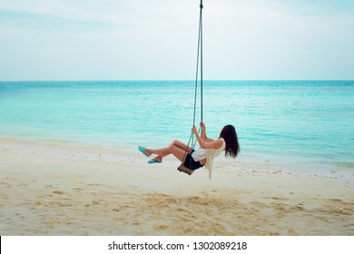 Swing on a palm tree. Beautiful island landscape with relaxing girl on a swing. Tropical resort.